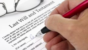 Close up of hand signing a Last Will and Testament document