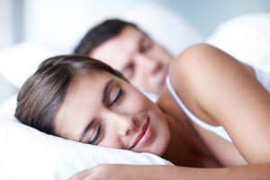 A happy young couple sleeping peacefully in bed